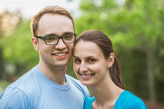 Portrait of young couple smiling together in park Stock Photo - Premium Royalty-Free, Image code: 653-07761541