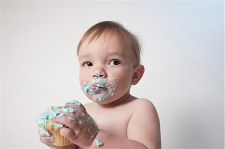 Cute baby boy with messy mouth looking away while holding cupcake against white background Stock Photo - Premium Royalty-Free, Code: 653-07761565