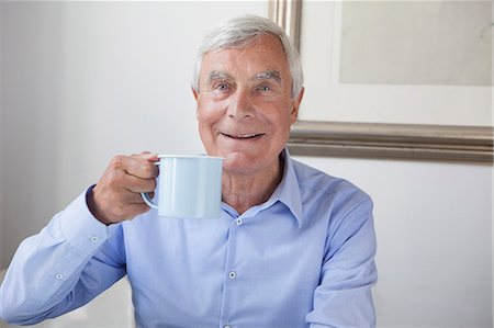 Portrait of happy senior man holding coffee mug at home Stock Photo - Premium Royalty-Free, Code: 653-07761607