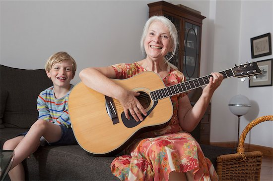 Portrait of boy sitting with grandmother playing guitar on sofa at home Stock Photo - Premium Royalty-Free, Image code: 653-07761609