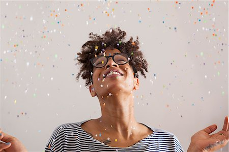 Happy young woman with confetti falling on her over gray background Stock Photo - Premium Royalty-Free, Code: 653-07761632