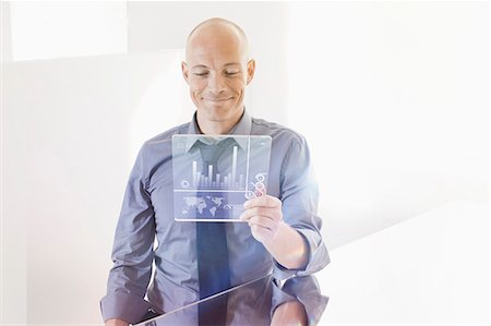 Smiling businessman looking at futuristic digital tablet at desk in office Stock Photo - Premium Royalty-Free, Code: 653-07883088
