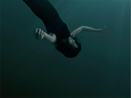 dead body floating in water - A woman with closed eyes and blank expression, sinking underwater Stock Photo - Premium Royalty-Free, Code: 653-08126097