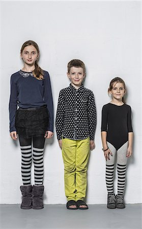 Full length portrait of smiling brother with sisters standing side by side against wall Stock Photo - Premium Royalty-Free, Code: 653-08126173