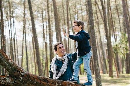 Happy father assisting son in climbing tree at forest Stock Photo - Premium Royalty-Free, Code: 653-08126376