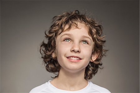 Close-up of thoughtful boy over gray background Stock Photo - Premium Royalty-Free, Code: 653-08171898