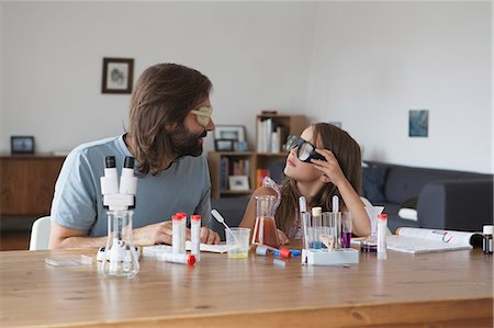 Father and daughter doing science experiment at table Stock Photo - Premium Royalty-Free, Code: 653-08276624