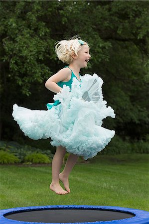 dress up girl - Happy girl bouncing on trampoline Stock Photo - Premium Royalty-Free, Code: 653-08276710