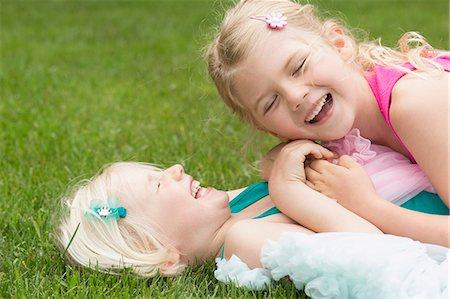 Happy girl lying on sister in backyard Stock Photo - Premium Royalty-Free, Code: 653-08276711