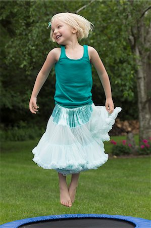 dress up girl - Happy girl jumping on trampoline Stock Photo - Premium Royalty-Free, Code: 653-08276720