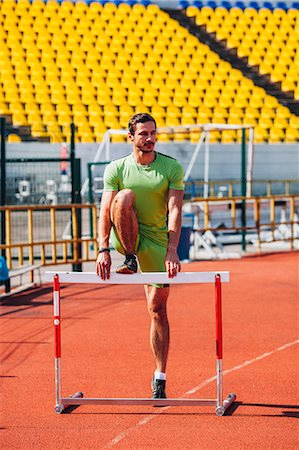 Full length of track and field athlete warming up on hurdle at sports track Stock Photo - Premium Royalty-Free, Code: 653-08382250