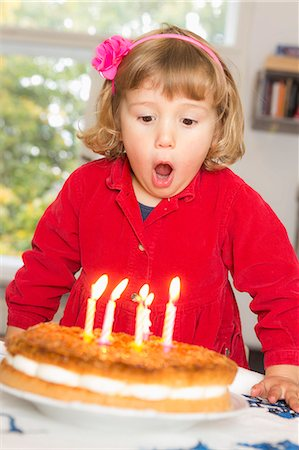Cute girl blowing birthday candles at table Stock Photo - Premium Royalty-Free, Code: 653-08382566