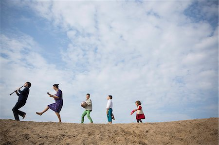 Low angle view of family enjoying on sand dune against cloudy sky Stock Photo - Premium Royalty-Free, Code: 653-08382577