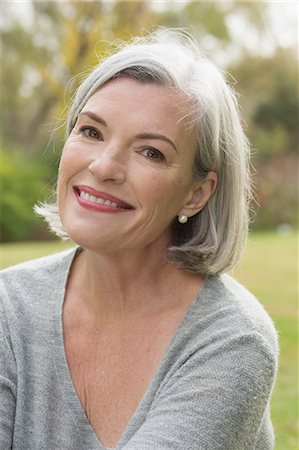 Close-up portrait of mature woman smiling at park Stock Photo - Premium Royalty-Free, Code: 653-08541582