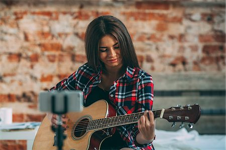 Smart phone in monopod with woman playing guitar at home Stock Photo - Premium Royalty-Free, Code: 653-08541597