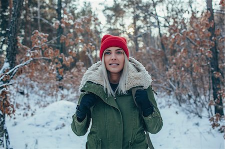 Young woman wearing knit hat and jacket while looking away Stock Photo - Premium Royalty-Free, Code: 653-08541632