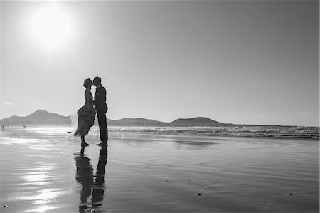 silhouette black and white - Full length side view of bride and groom kissing at beach against clear sky Stock Photo - Premium Royalty-Free, Code: 653-08634098