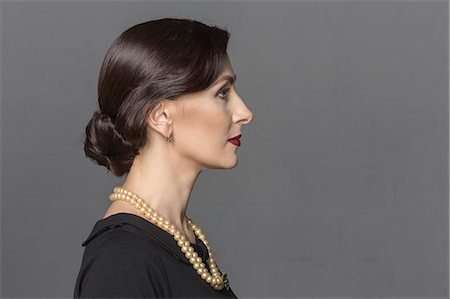 Profile view of beautiful woman against gray background Stock Photo - Premium Royalty-Free, Code: 653-08633848