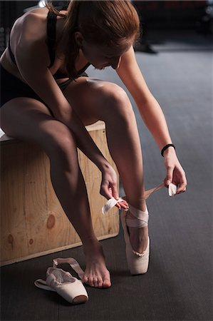 Teenage girl tying ballet shoe at gym Stock Photo - Premium Royalty-Free, Code: 653-08633909