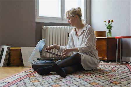 photograph - Full length of woman playing record while sitting at home Stock Photo - Premium Royalty-Free, Code: 653-08633943