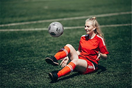 Confident soccer player playing with ball on field Stock Photo - Premium Royalty-Free, Code: 653-08728714