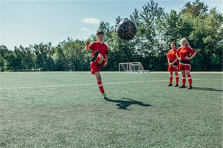 female playing soccer - Soccer player kicking ball while friends stand nearby on field Stock Photo - Premium Royalty-Free, Code: 653-08728717