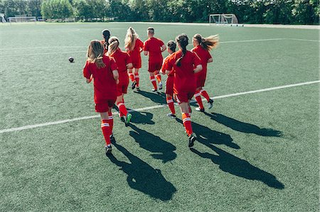 Rear view of soccer players running on field Stock Photo - Premium Royalty-Free, Code: 653-08728711