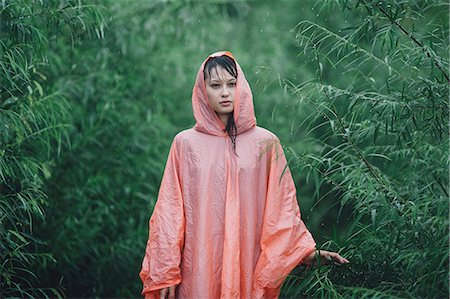 Young woman wearing raincoat standing amidst plants during rainy season Stock Photo - Premium Royalty-Free, Code: 653-08728877