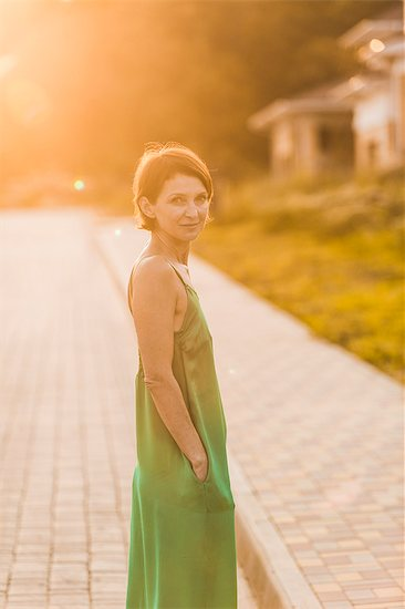 Side view of woman wearing dress standing on sidewalk during sunny day Stock Photo - Premium Royalty-Free, Image code: 653-08728912