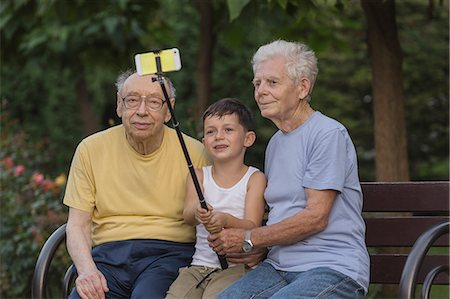 Smiling boy taking selfie by monopod with grandfathers at park bench Stock Photo - Premium Royalty-Free, Code: 653-08728965