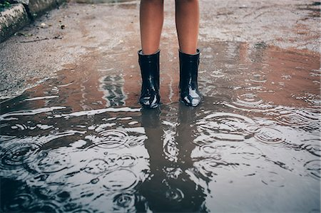female 16 year old feet - Low section of teenager wearing rubber boot standing in puddle during rain Stock Photo - Premium Royalty-Free, Code: 653-09007054
