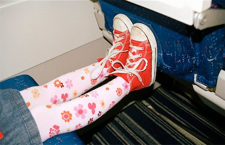 stocking feet - Child's feet against airplane seat Stock Photo - Premium Royalty-Free, Code: 653-01654147