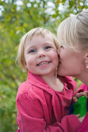 daughter kissing mother - A mother kissing her daughter, smiling Stock Photo - Premium Royalty-Free, Code: 653-01656233