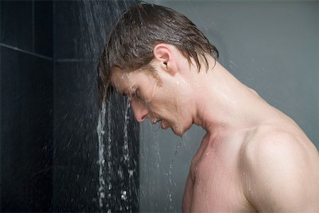 Man standing in shower and looking down Stock Photo - Premium Royalty-Free, Code: 653-01656512