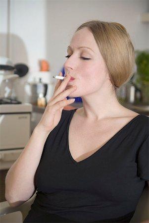 Woman sitting in kitchen smoking a cigarette Stock Photo - Premium Royalty-Free, Code: 653-01657382