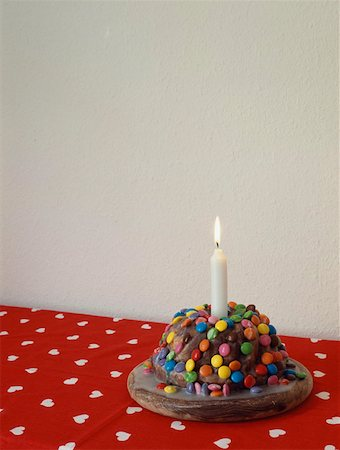 Candy covered chocolate cake with one candle Stock Photo - Premium Royalty-Free, Code: 653-01657735
