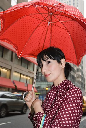 Young woman wearing a polka dot dress and holding a red umbrella in city street, New York City Stock Photo - Premium Royalty-Free, Code: 653-01657881