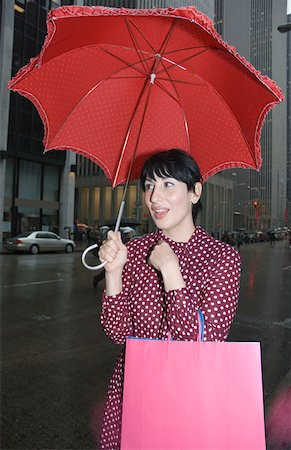 Young woman standing on street holding an umbrella and shopping bags, New York City Stock Photo - Premium Royalty-Free, Code: 653-01657904