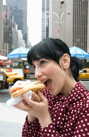 Young woman standing on street and eating a hot dog, New York City Stock Photo - Premium Royalty-Free, Code: 653-01657902