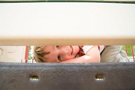 Young boy peeking through play equipment Stock Photo - Premium Royalty-Free, Code: 653-01658309