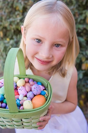 Young girl holding basket full of Easter eggs Stock Photo - Premium Royalty-Free, Code: 653-01658385
