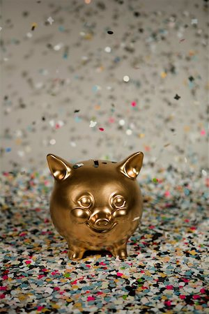 party celebration paper confetti - Gold piggy bank amongst floating confetti Stock Photo - Premium Royalty-Free, Code: 653-01659868