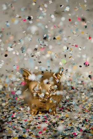 party celebration paper confetti - Gold piggy bank amongst floating confetti Stock Photo - Premium Royalty-Free, Code: 653-01659874