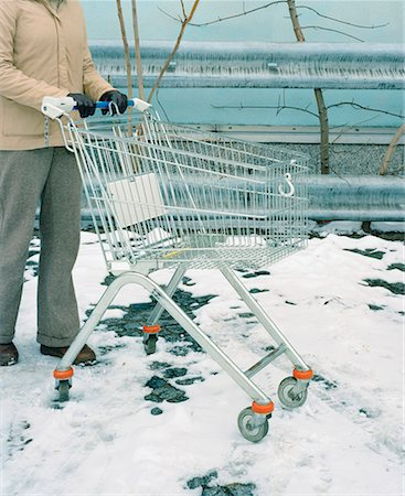 empty shopping cart - A person pushing a shopping cart in the snow Stock Photo - Premium Royalty-Free, Code: 653-01653038