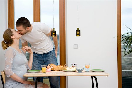 pregnant women kissing - Pregnant couple kissing over breakfast Stock Photo - Premium Royalty-Free, Code: 653-01664322