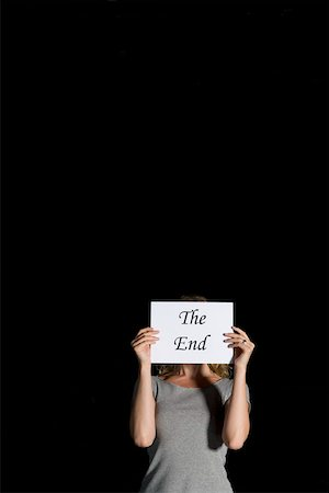 A woman holding a sign for 'The End' Stock Photo - Premium Royalty-Free, Code: 653-01665885