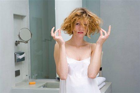 Woman looking worried in bathroom Stock Photo - Premium Royalty-Free, Code: 653-01661398