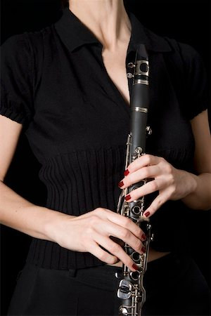 finger holding a key - Woman holding a clarinet Stock Photo - Premium Royalty-Free, Code: 653-01662404