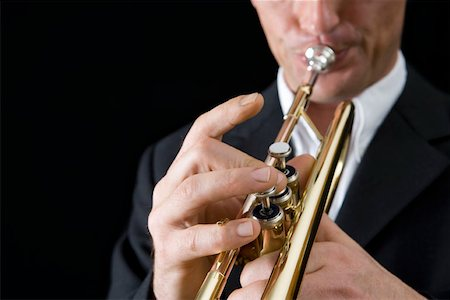 finger holding a key - Man playing a trumpet Stock Photo - Premium Royalty-Free, Code: 653-01662449