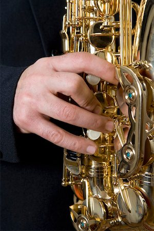 finger holding a key - Detail of a man playing the saxophone Stock Photo - Premium Royalty-Free, Code: 653-01662455